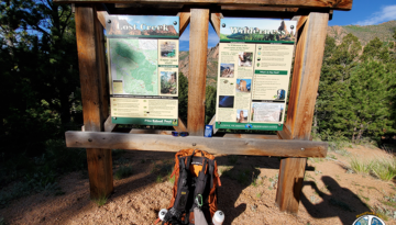 Trail Head sign, Lost Creek Wilderness information with a map. Also showing off my Optic Nerve Sunglasses, a RX Bar and my Osprey Pack.
